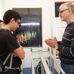 Prof. Lutz Köpke erklärt einem interessierten Besucher ein Neutrinoereignis, gemessen am IceCube Experiment am Südpol. Das Poster im Hintergrund zeigt das Ereignis.